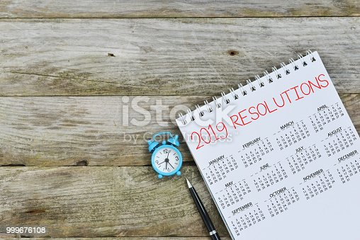 istock 2019 Resolutions on calendar  on wooden background, with empty space to insert text 999676108