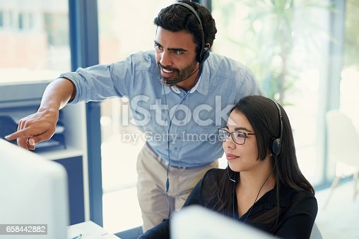 Cropped shot of two call centre agents working together in an office