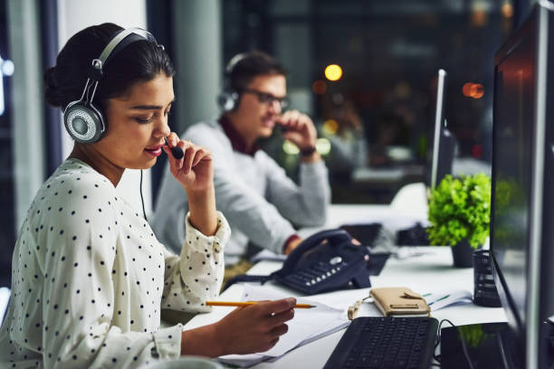 Resolving issues with speed for their clients Shot of young call centre agents working late in an office call centre photos stock pictures, royalty-free photos & images