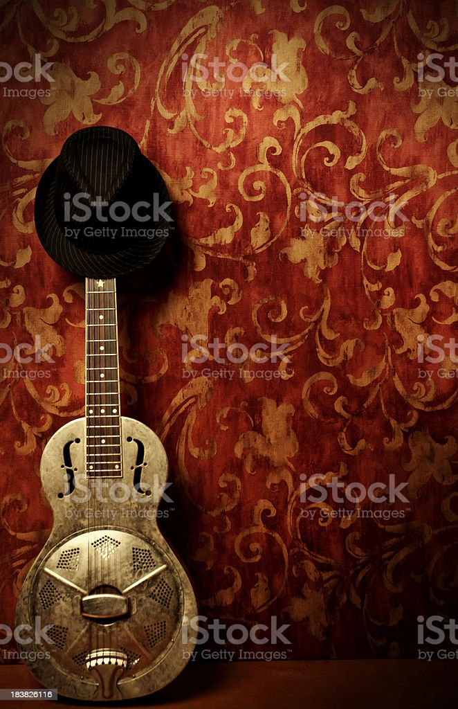 Resonator Guitar with Hat on Red Background stock photo