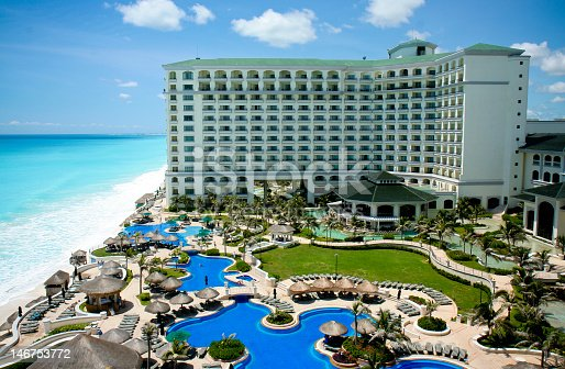Aerial view of a Cancun resort.  There are several large pool areas and a multi-level hotel at this resort.  An ocean and sandy beach can be seen to the left of the hotel.