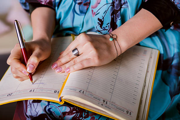 respectable woman is writing notes and planning schedule. stock photo
