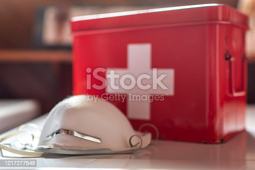 N95 face mask next to a red first aid kit.