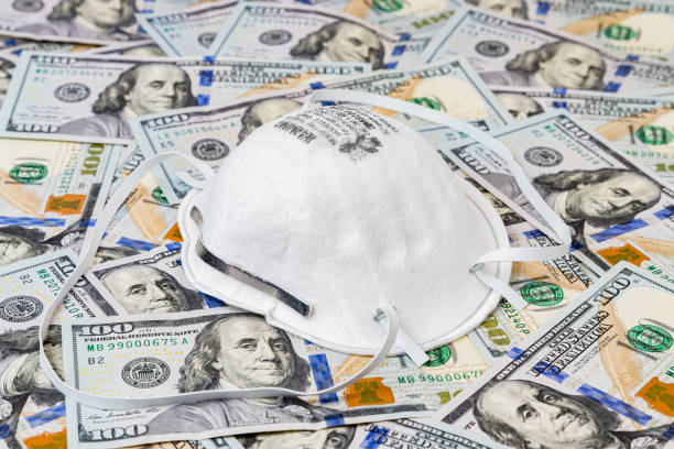 N95 respirator mask with 100 dollar bills. Concept of supply and demand, shortage and price gouging due to Covid-19 coronavirus worldwide pandemic stock photo