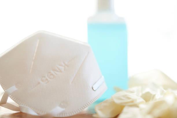 atemschutzmaske desinfektionsmittel flasche und einmalhandschuhe - ffp2 stock-fotos und bilder