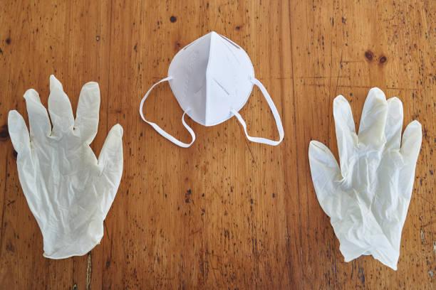 atemschutzmaske kn95 zwischen zwei einweghandschuhen - ffp2 stock-fotos und bilder