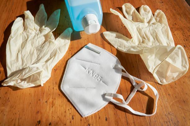 atemschutzmaske kn95, einweghandschuhe und flasche mit desinfektionsmittel - ffp2 stock-fotos und bilder