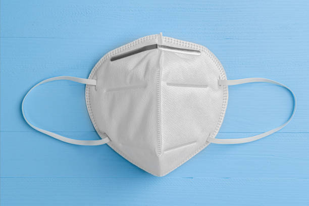 n95 respiratory mask on a blue wooden background with elastic bands for the ears - ffp2 imagens e fotografias de stock
