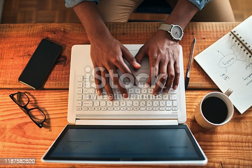 High angle shot of an unrecognizable businessman sitting alone in his home office and typing on his laptop