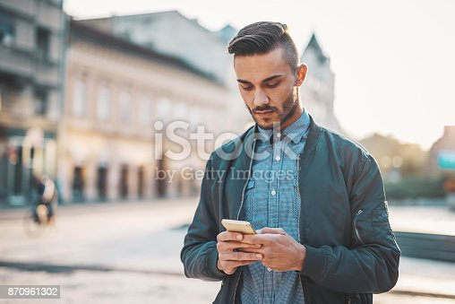 Young man in casual clothing in downtown on warm autumn day. Man is using means of digital communication and software apps for doing business.