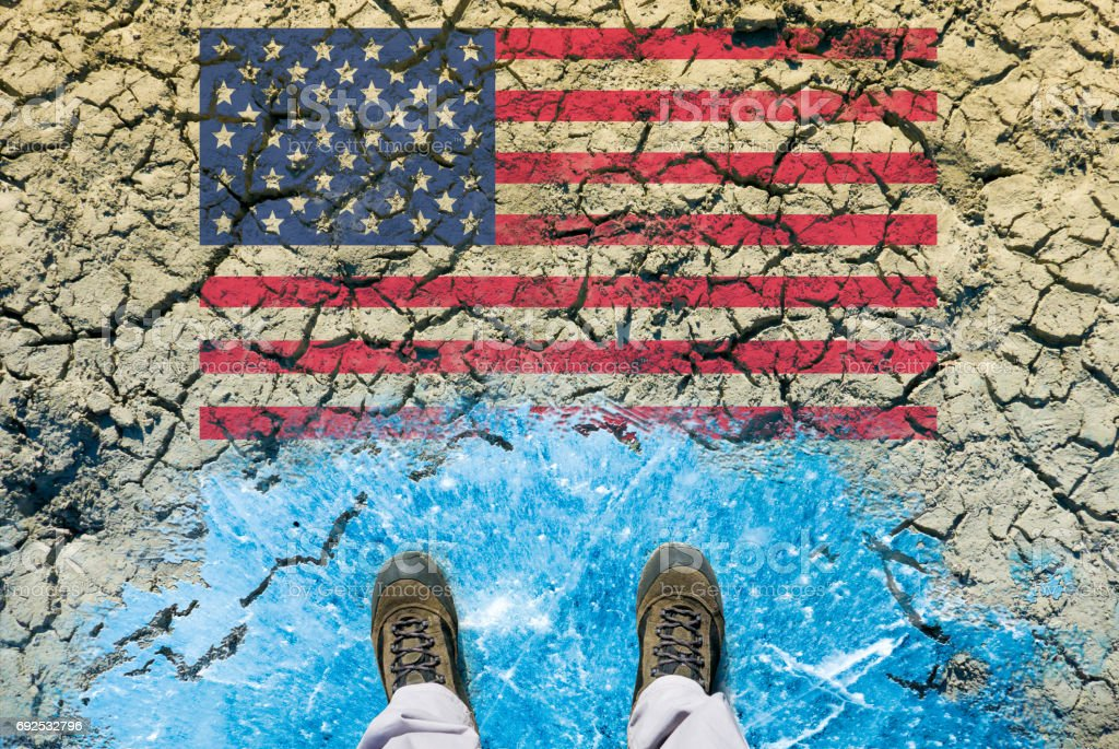 Responsibility of USA on global climate policy and greenhouse effect. Man standing on ice in front of the desert wasteland with american flag. stock photo