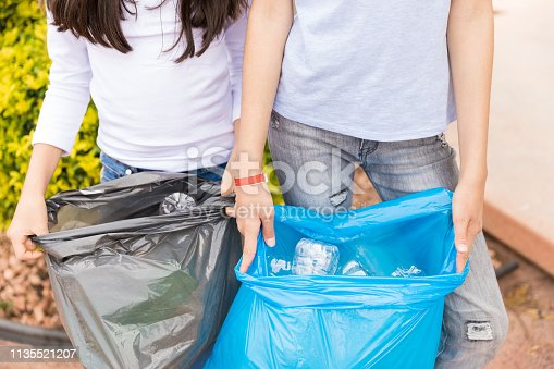 Midsection of girls in casuals showing waste in garbage bags at yard
