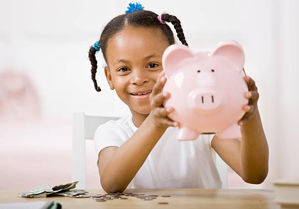 Responsible girl putting money into piggy bank for future saving stock photo