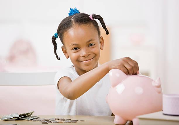 Responsible girl putting money into piggy bank for future savings stock photo