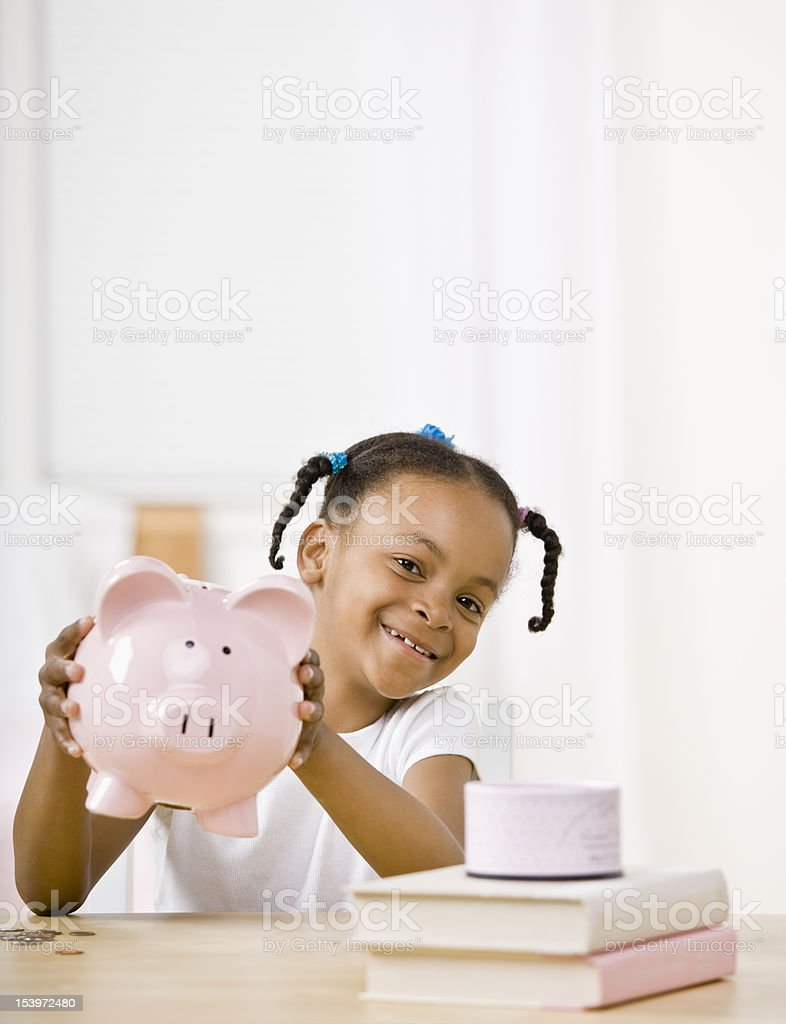 Responsible girl putting money into piggy bank for future savings stock photo