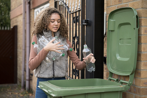 Front view of 17 year old mixed race girl carrying armful of plastic bottles and placing them in recycling bin outside family home.