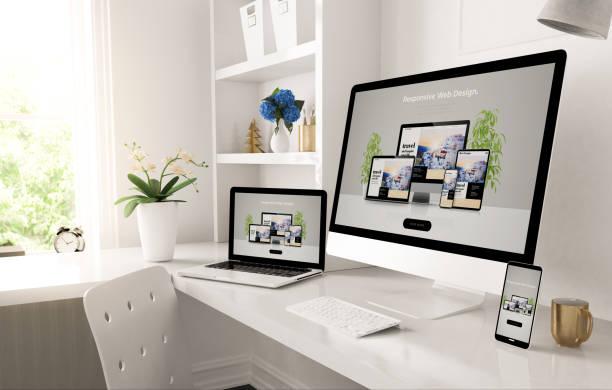 responsive devices on home desktop showing web design website stock photo