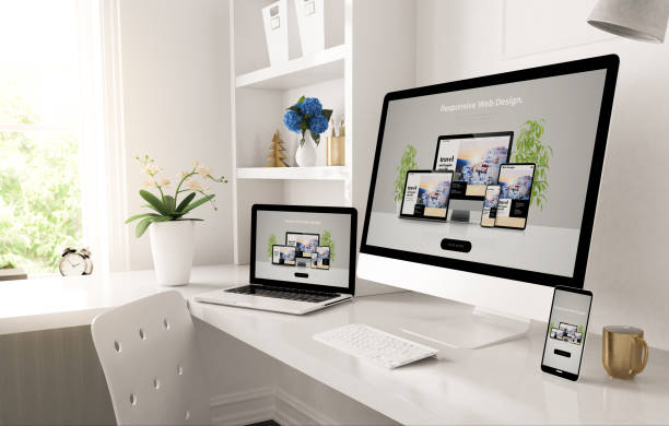 responsive devices on home desktop showing web design website stock photo