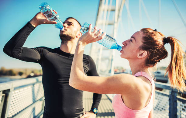 Rest after exercising. Thirsty sportsman and sportswoman drinking water after training outdoors. Fitness, sport, lifestyle concept stock photo