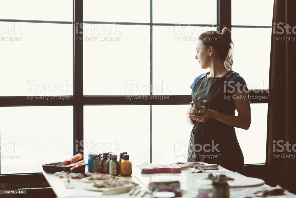 Rest and contemplation time. Artist inspiration. Craft woman with mug...