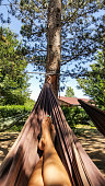 the girl is lying in a hammock. woman resting in a hammock in nature. Girl's legs in hammock