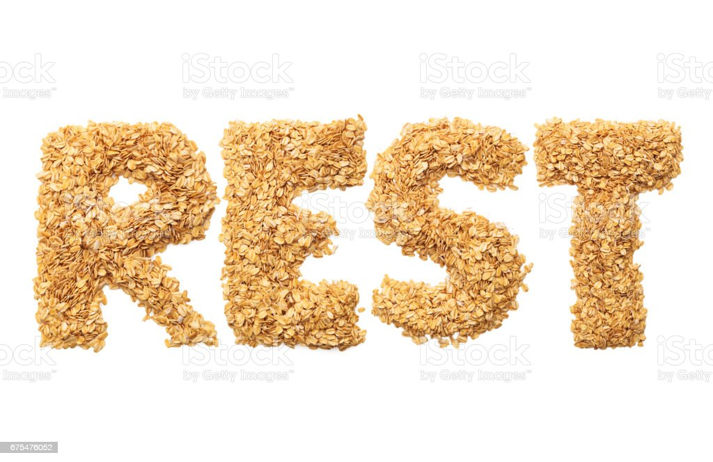 'Rest' written with oat grains word. Shape of oatmeal flakes on isolated white background stock photo