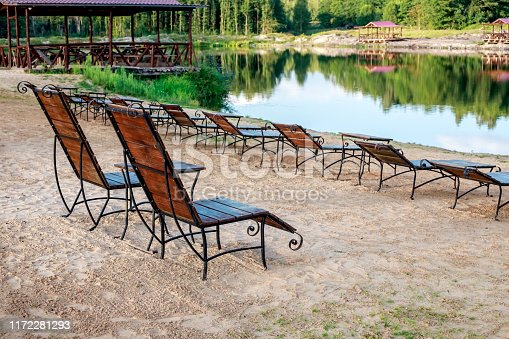Rest zone. Wooden sun loungers and chairs with tables stand on the beach by the lake, facing the lake. Belarus