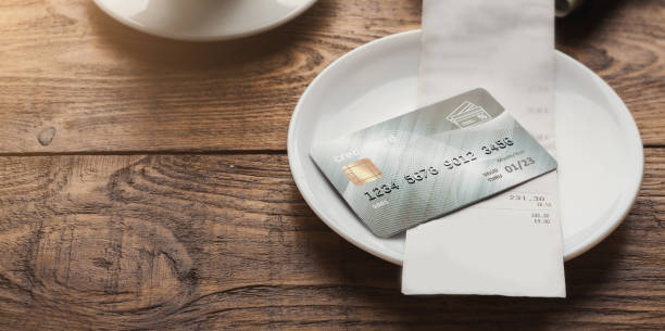 Restaurant bill and credit card on wooden table stock photo