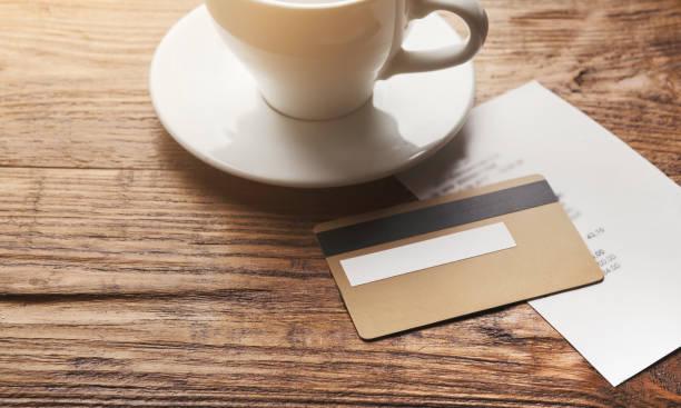 restaurantrechnung und kreditkarte auf holztisch - teller kaufen stock-fotos und bilder