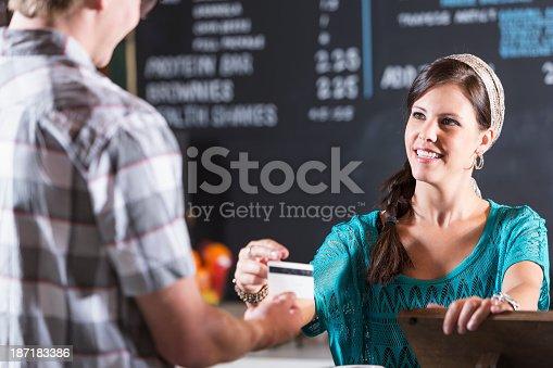 istock Restaurant cashier reaches for customer card 187183386