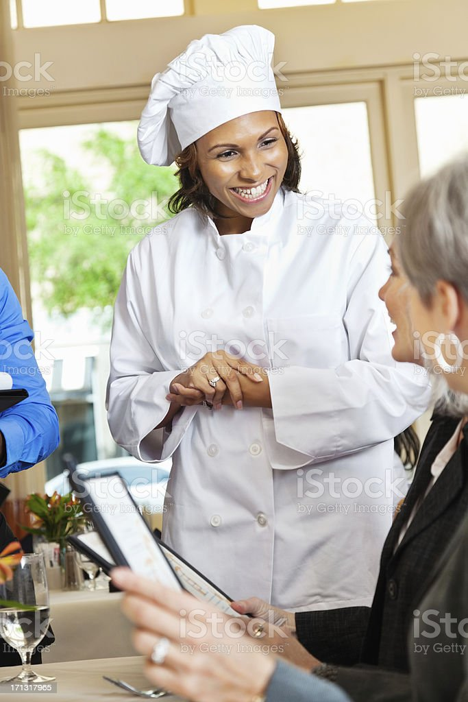 Restaurant chef helping customers order from menu royalty-free stock photo