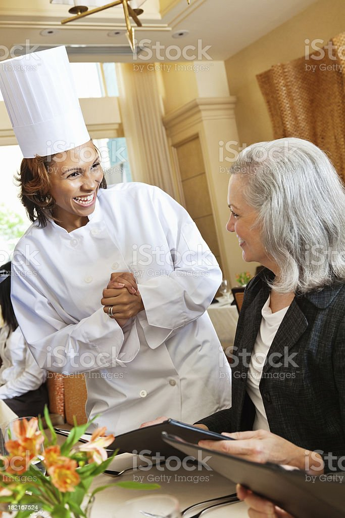 Restaurant chef helping customers order from menu stock photo