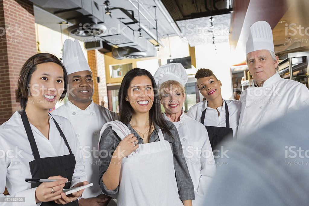 Restaurant chefs and waitstaff getting instructions from manager in kitchen stock photo