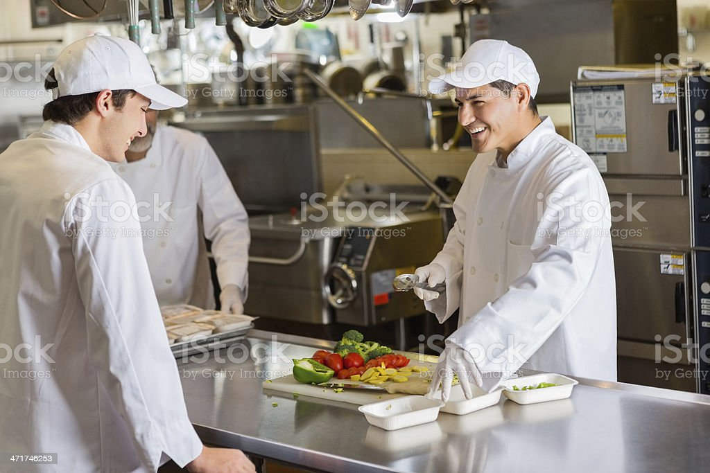 Restaurant chefs preparing food in commercial kitchen royalty-free stock photo
