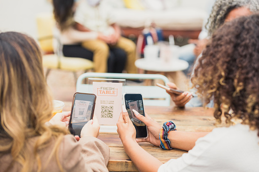 While dining out at an outdoor cafe, women use a qr code to download the restaurant's menu. They are dining out during COVID-19. The qr code is seen on their device screens.