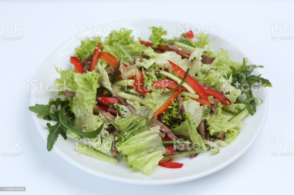 restaurant dish, green salad with cucumbers, red pepper,bacon and...