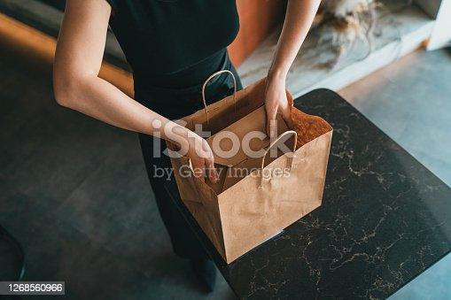 A restaurant employee checking and preparing take out food orders