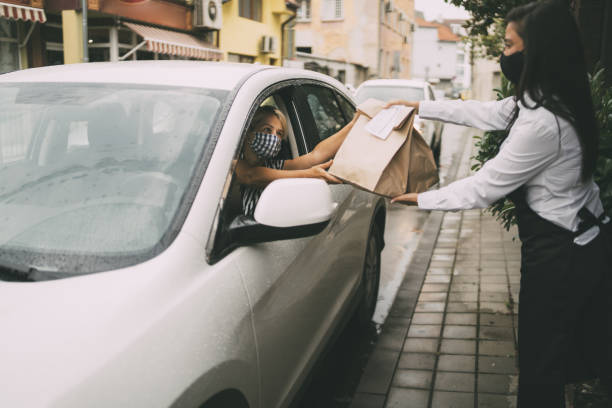 Restaurant employee delivers packed food to a female driver. Waitress wearing protective face mask is giving disposable package with food  to pretty smiling female driver. Reopening after COVID-19 concepts. curbsidepickup stock pictures, royalty-free photos & images
