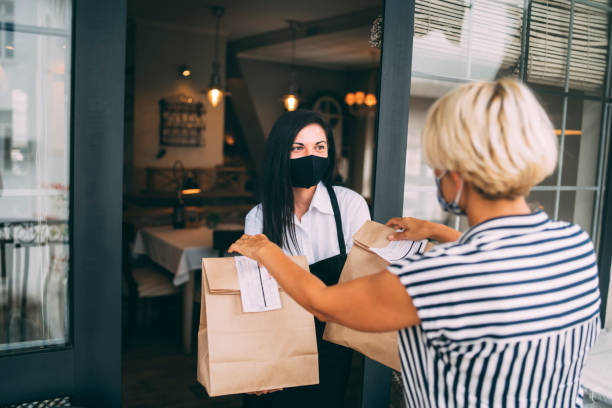 Restaurant employer giving packed food away to a customer. Reopening after COVID-19 quarantine concepts.