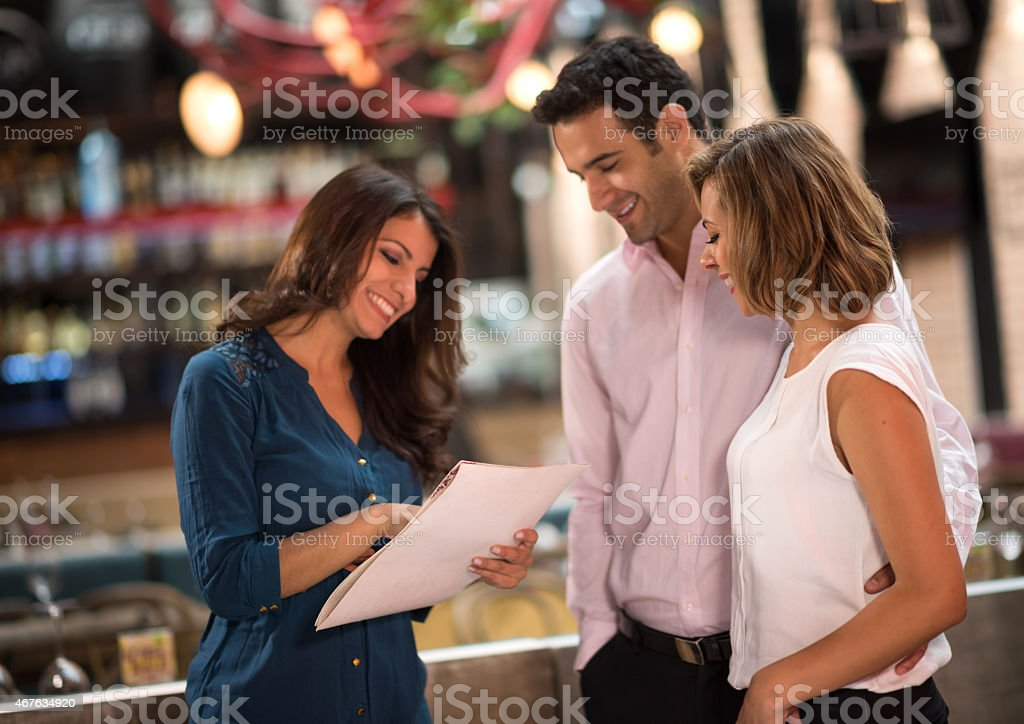 Restaurant hostess welcoming customers stock photo