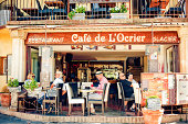"""""""Paris, France - July 13, 2012: People sitting in a restaurant in Roussillon - Provencial touristic town famous for its ochra cliffs"""""""