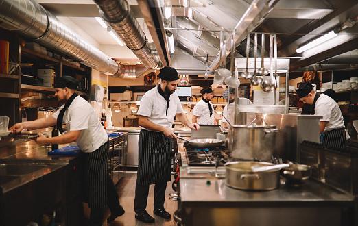 Restaurant kitchen crew preparing food.