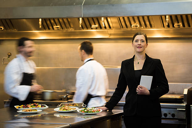 restaurant manager in a commercial kitchen - busy restaurant kitchen stock pictures, royalty-free photos & images