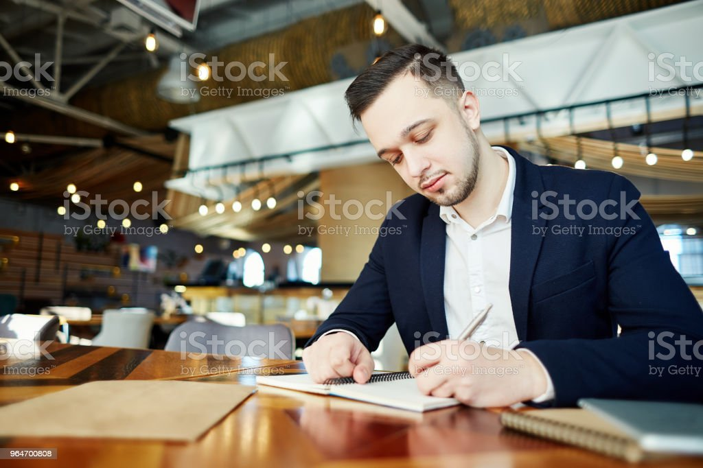 Restaurant manager in shirt and jacket sitting at table and making notes in his personal organizer royalty-free stock photo