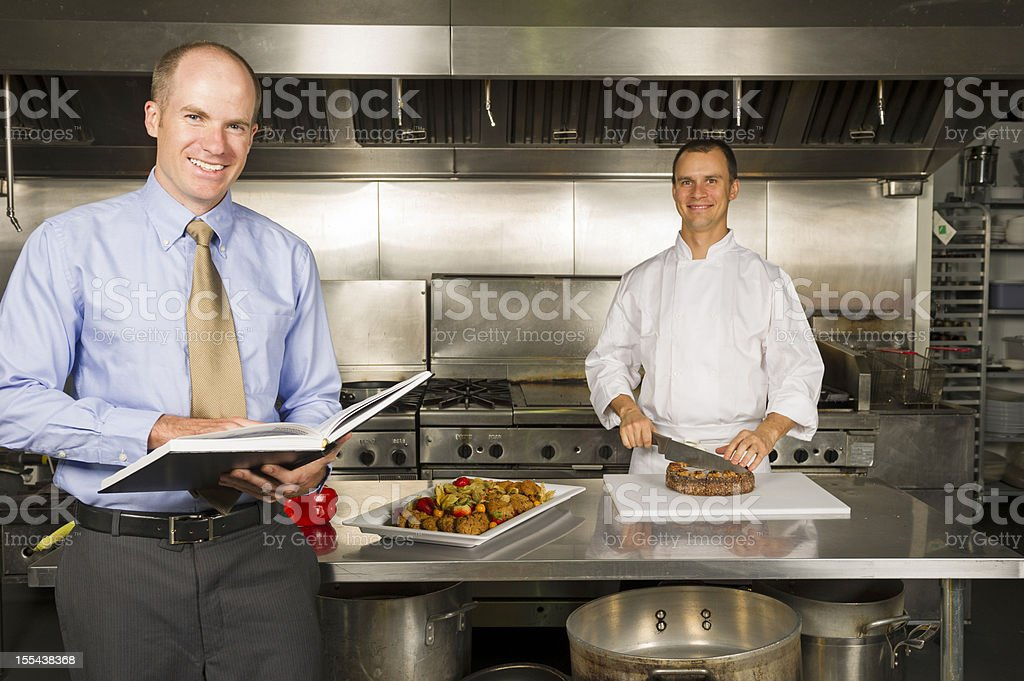 A restaurant manager stood in the kitchen with the chef royalty-free stock photo