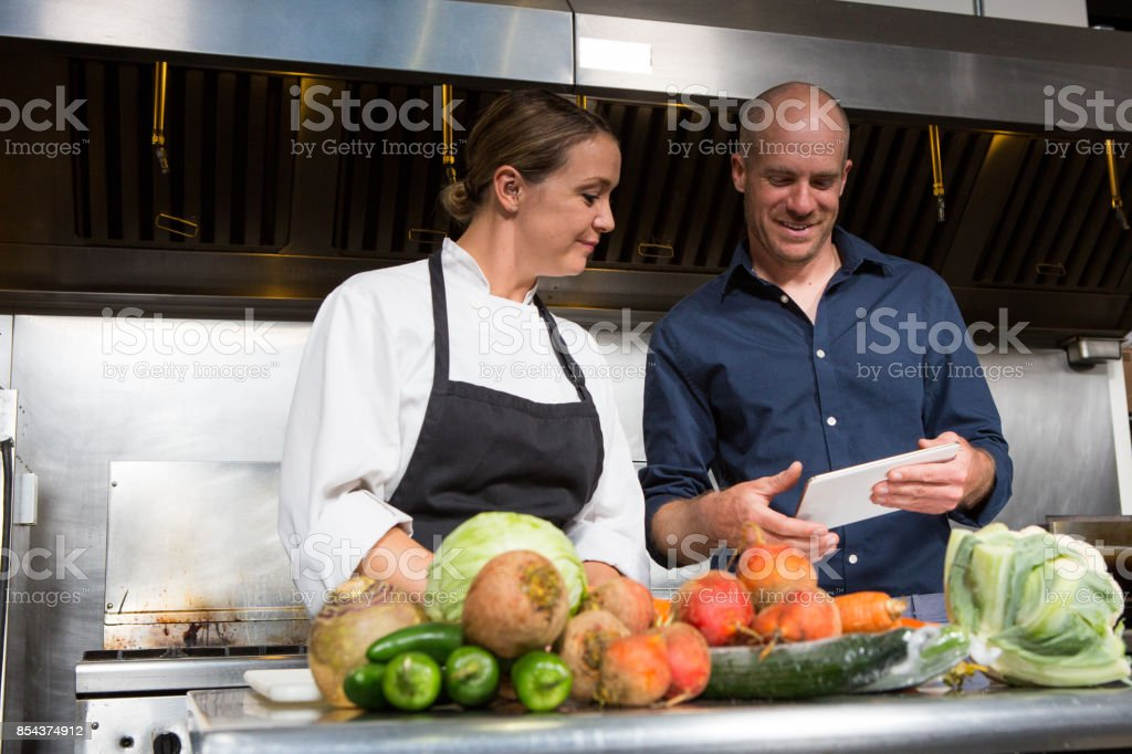 Restaurant manager working together with a professional female chef stock photo