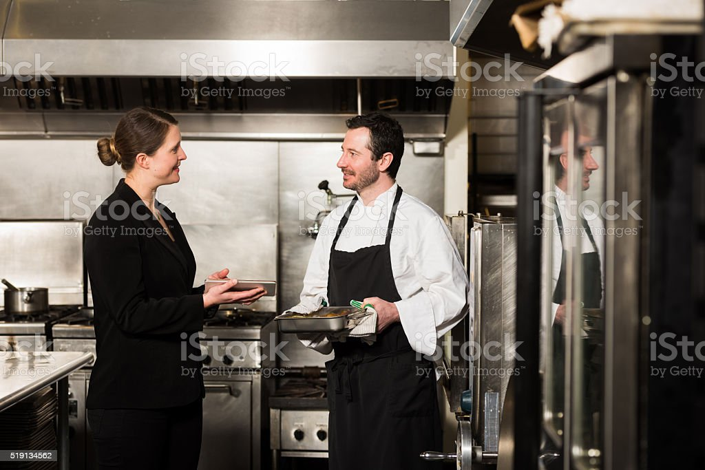 Exterior: Restaurant Manager Working With A Professional Chef Stock