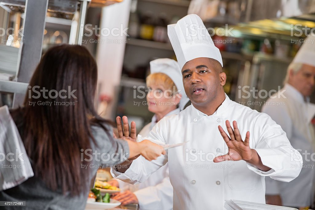 Restaurant manager yelling at chefs in kitchen with late tickets stock photo