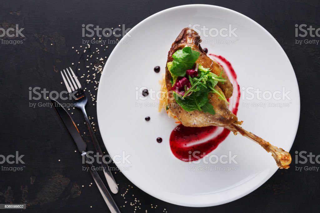 Restaurant meals. Duck confit with vegetables on black background stock photo