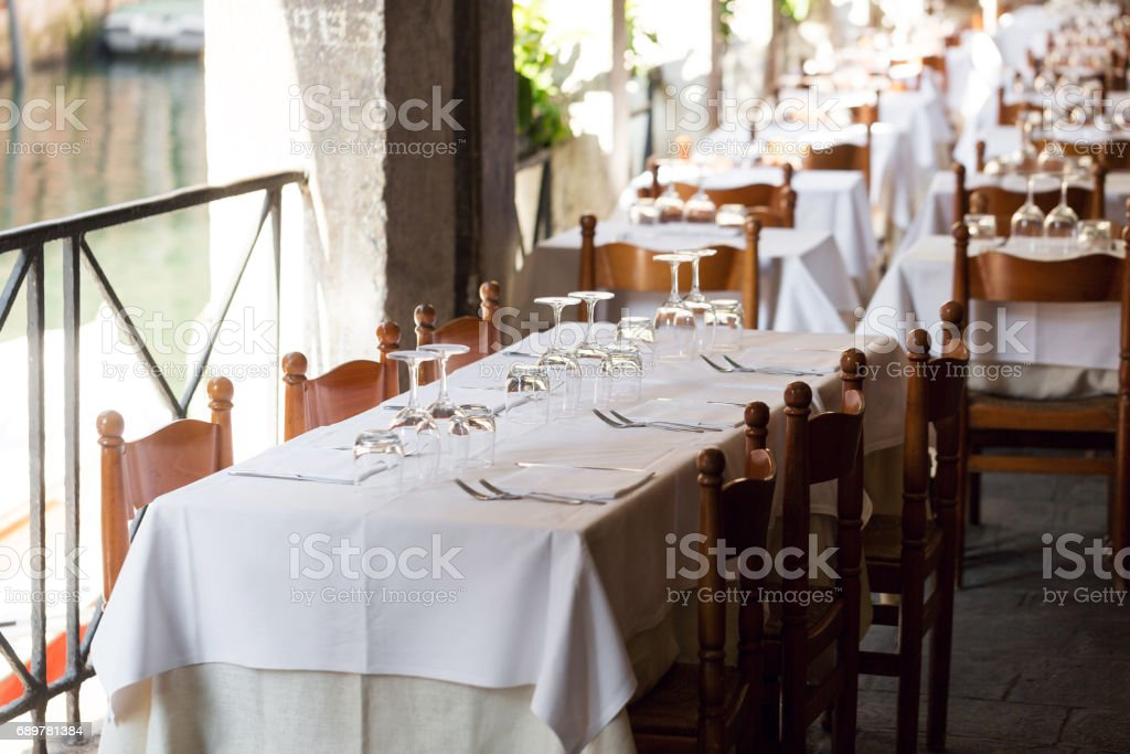 restaurant on the canal Venice. table setting for a lovey dinner. Empty glasses set in cafe. Part of interior. napkins, plates, and cutlery. stock photo